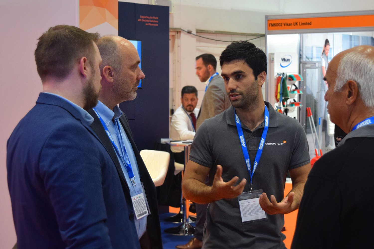 commusoft ceo, jason, talking with 3 men at the facilities show
