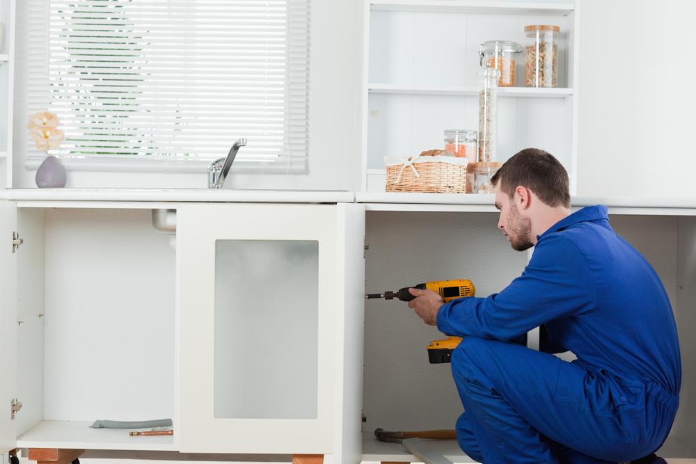 Good looking handyman fixing a door in a kitchen