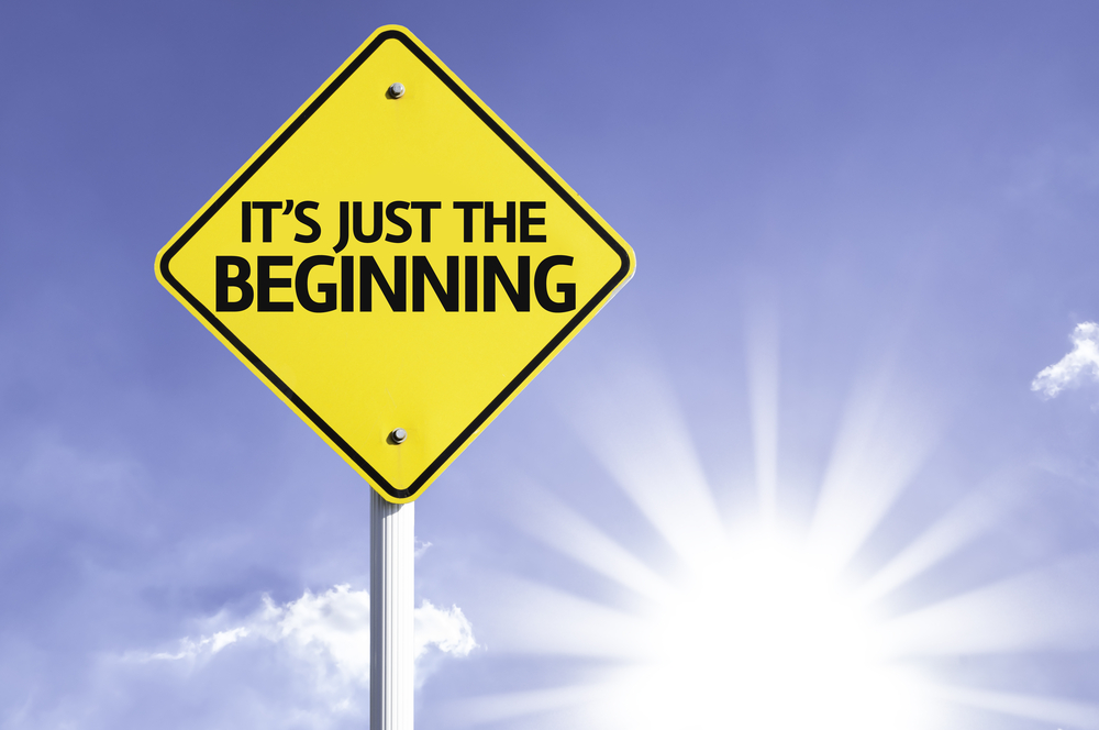 Its Just The Beginning road sign with sun background
