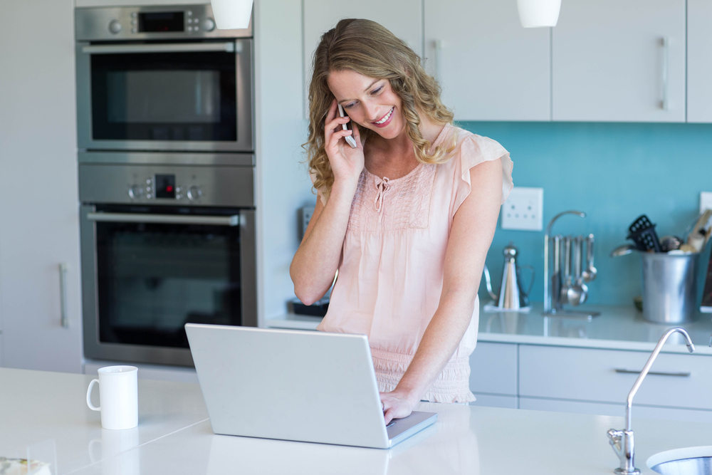 Pretty blonde on the phone using laptop at home in the kitchen