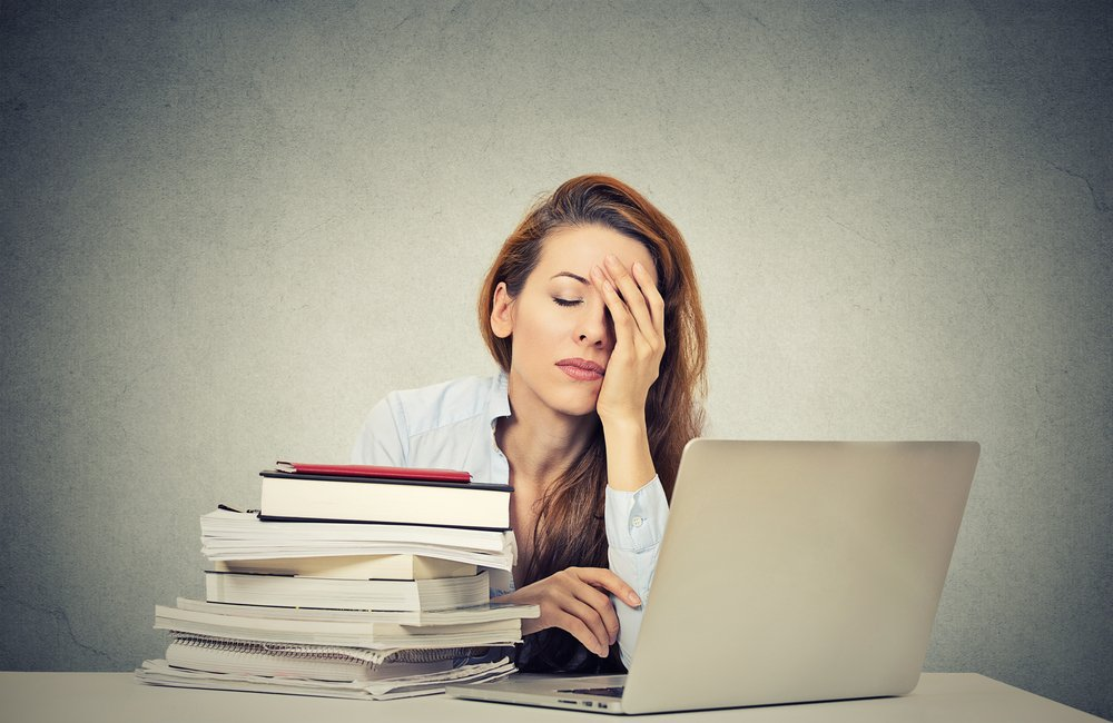 Too much work tired sleepy young woman sitting at her desk with books in front of laptop computer isolated grey wall office background. Busy schedule in college, workplace, sleep deprivation concept