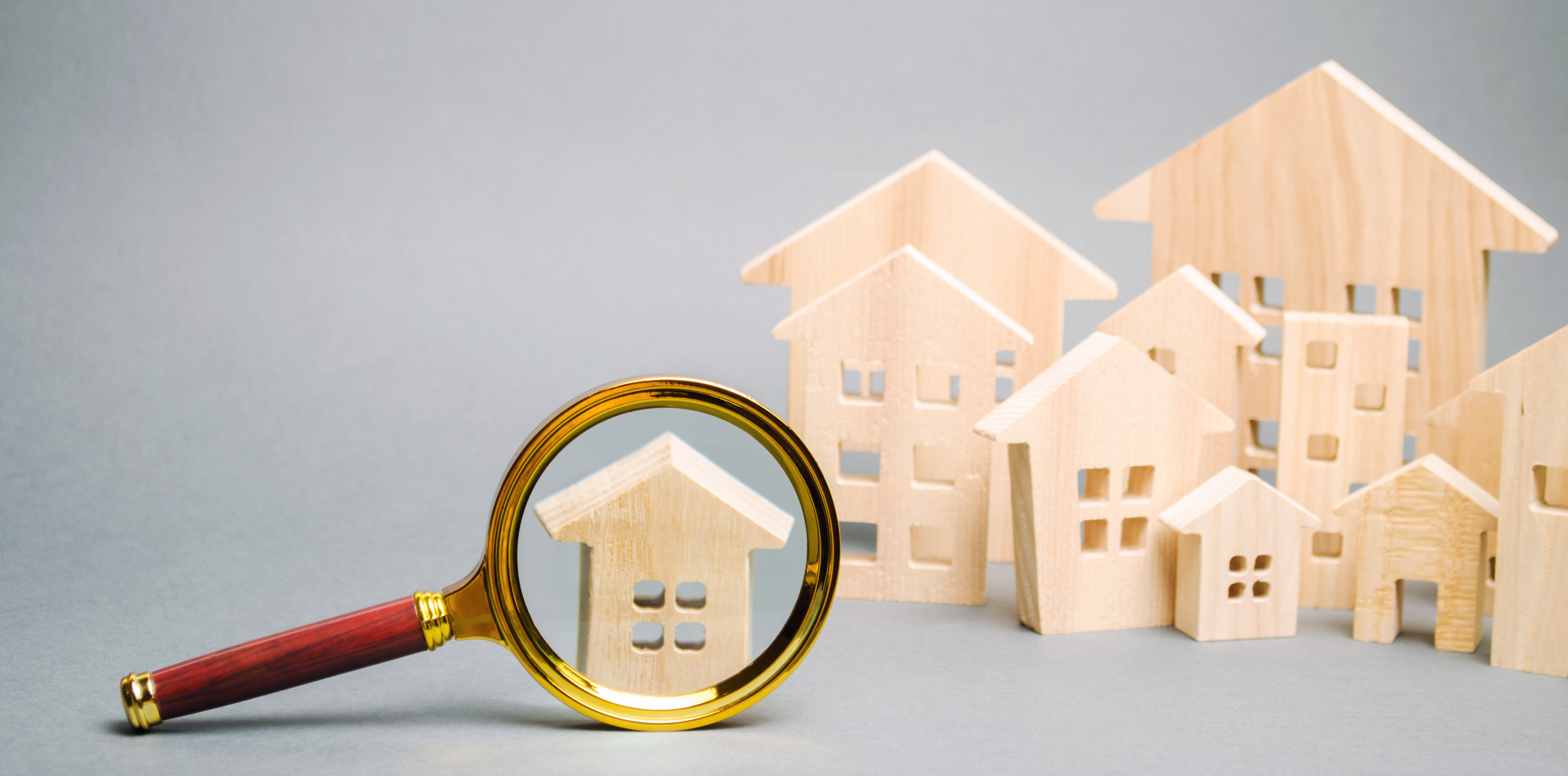 magnifying-glass-and-wooden-houses-J8JZTK8