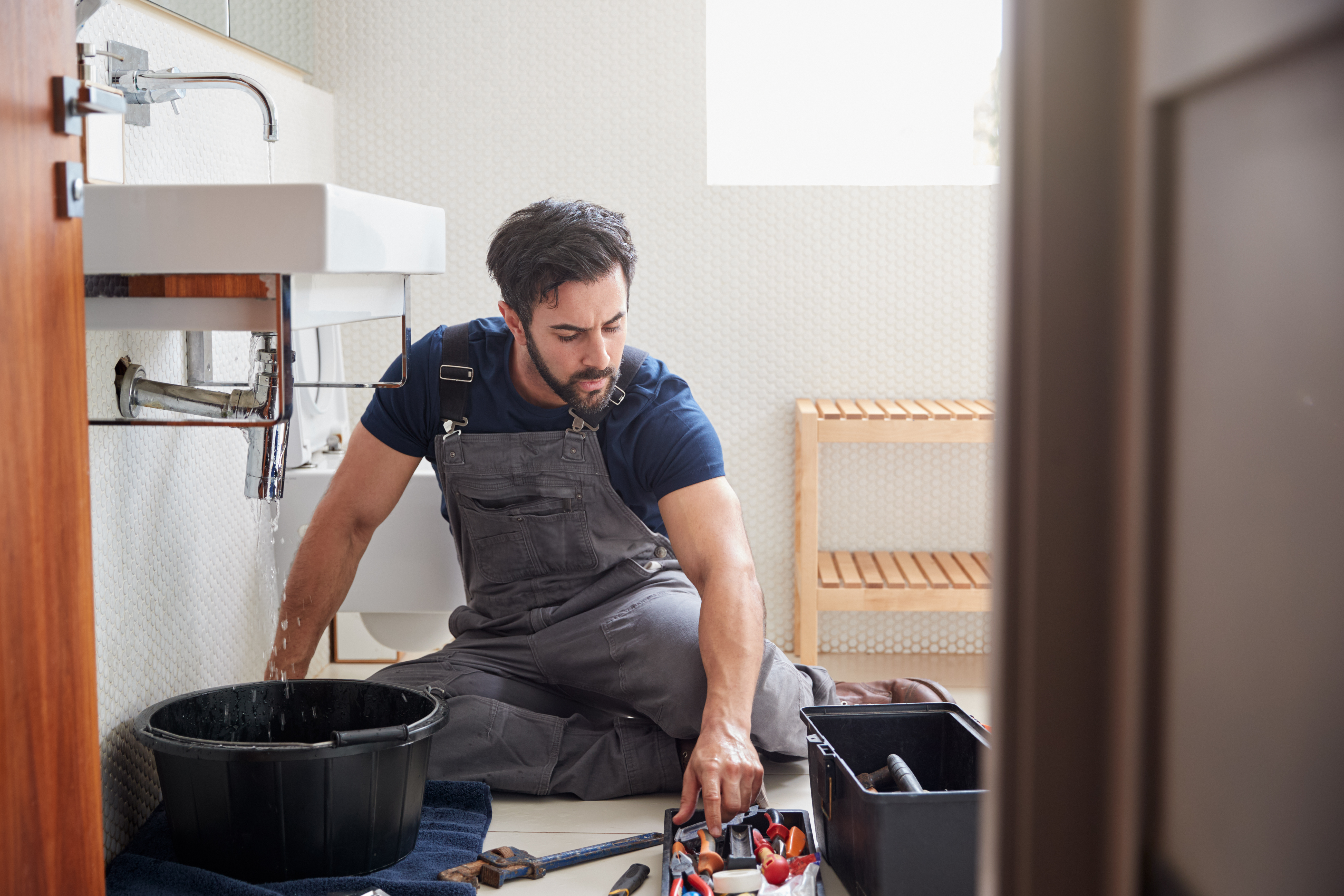 male-plumber-working-to-fix-leaking-sink-in-home-b-9ZH3FDD