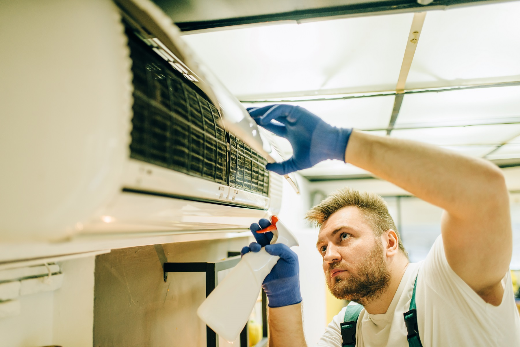 repairman-in-uniform-cleans-the-air-conditioner-3ZHES5W
