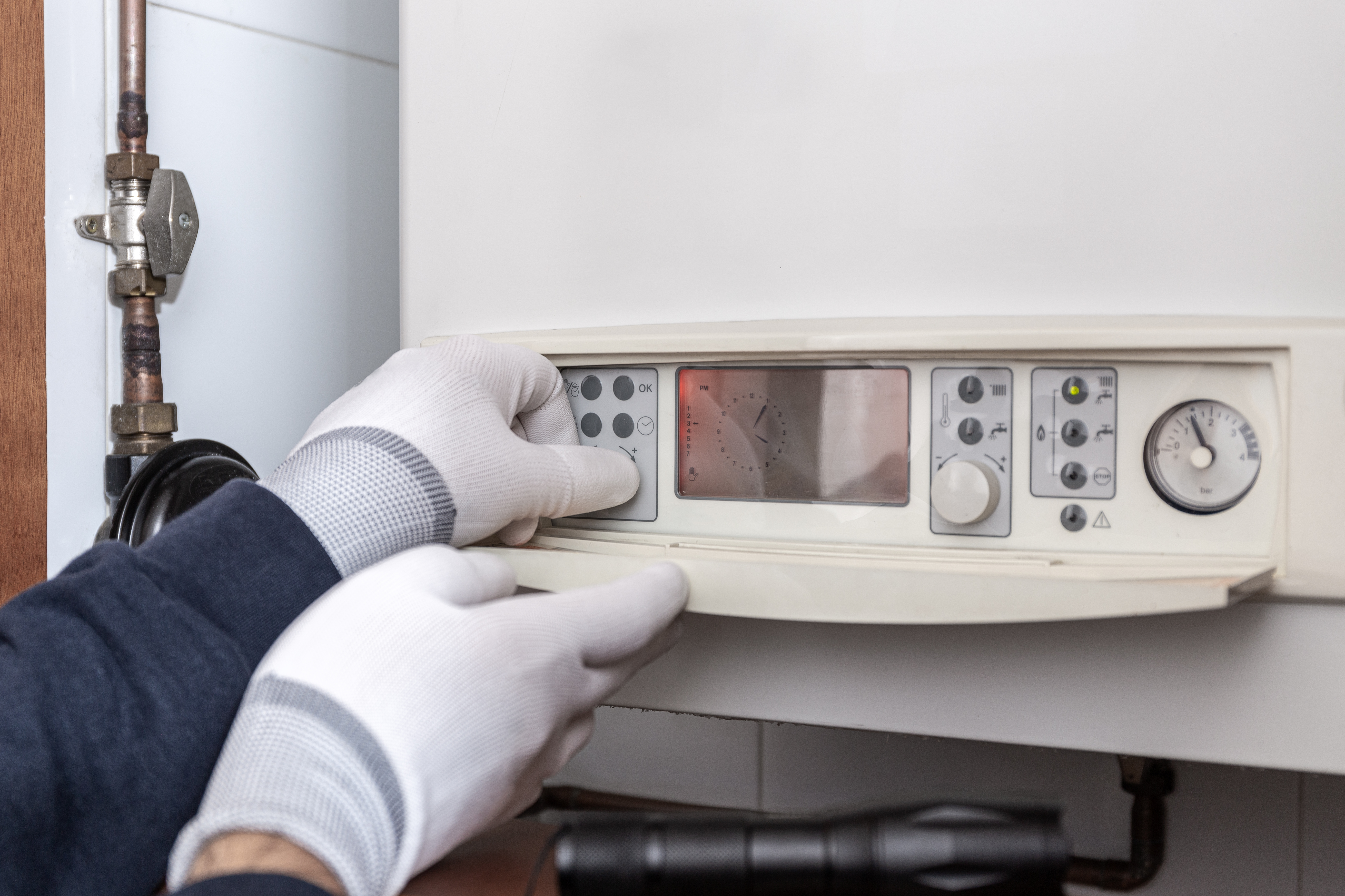 technician-servicing-heating-boiler-in-a-house-W64F4UV